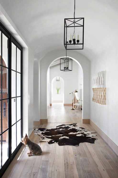 Light Filled Hallway With Arched Doorways White Walls And Hardwood Floors