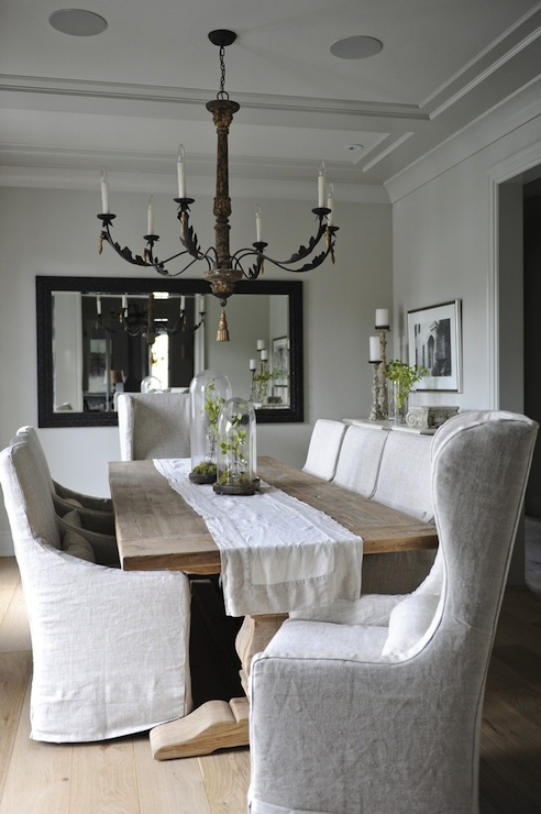 Beautiful Dining Room With Salvaged Wood Trestle Dining Table Lined With  Linen Slipcovered Arm Chairs And A Pair Of Wing Back Slipcovered End Chairs.