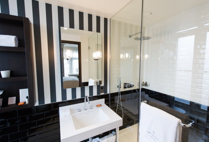 Black And White Bathroom Features Walk In Shower Accented With Beveled Subway Tiles On Top Half Of Walls Bottom