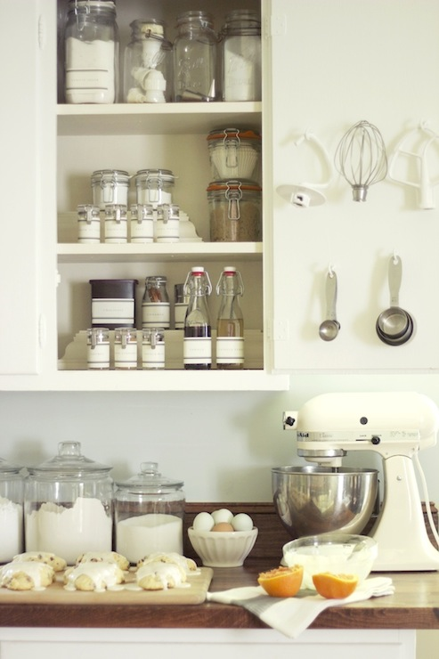 White Kitchen Cabinetry Pairs With Butcher Block Counters Which Hold A  White KitchenAid Mixer And Anchor Hocking Glass Canisters.