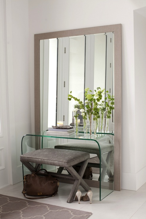 Gray Foyer With Gray X Bench Tucked Under Acrylic Waterfall Console Table  Framed By Gray Floor Mirror As Well As Gray Trellis Rug Layered Over White  Painted ...