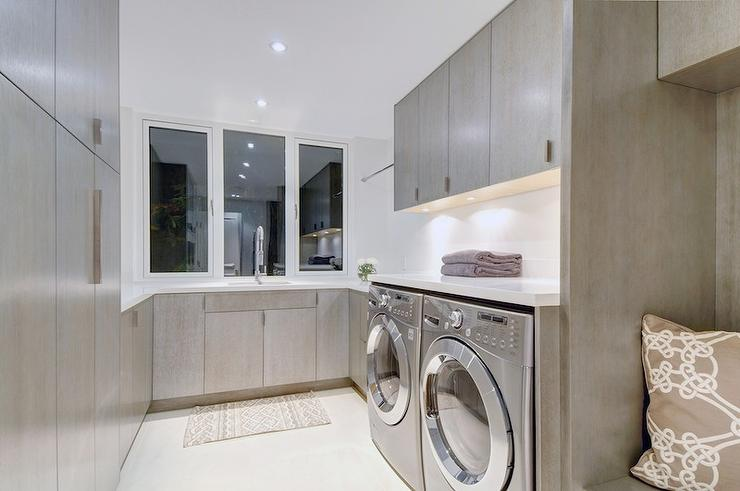 Gray Laundry Room Design With Frameless Gray Cabinets Paired With White Quartz Countertops