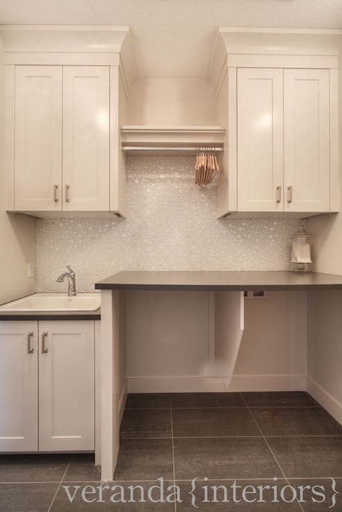 Stunning Laundry Room With Ceiling Height Cabinetry Pairing With Brushed Nickel Hardware And Gray Laminate Countertops