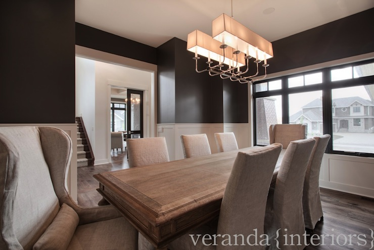 Elegant Dining Room With White Shaker Style Wainscoting And Dark Gray Walls.