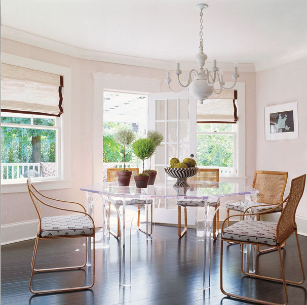 Lucite Dining Table Surrounded By Woven Chairs Over Dark Hardwood Floors Curved Room Features White And Brown Grosgrain Roman Shades