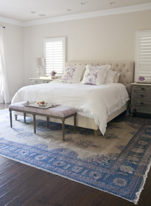 Chic bedroom with tan walls framing tan tufted headboard accented with white  Belgian linen ruffled bedding flanked by mother of pearl lamp and mother of. Blue and White Distressed Geometric Pattern Rug