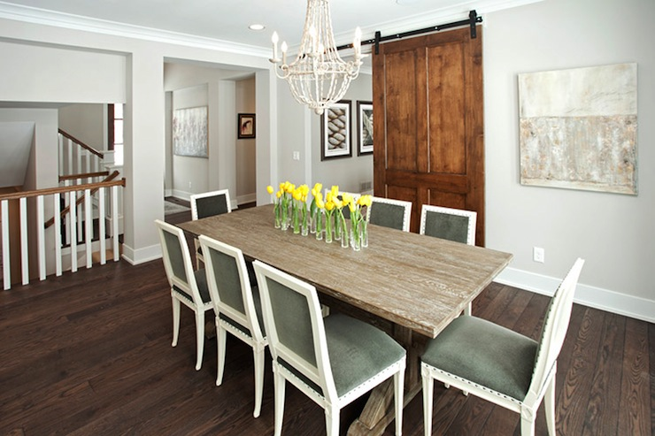chic dining room with white beaded chandelier over limed oak trestle dining table surround by green velvet dining chairs