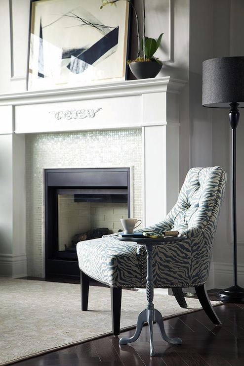 Chic Living Room With Abstract Art Over Glass Tiled Fireplace Next To White And Turquoise Blue Zebra Chair Paired Accent Table Black Floor