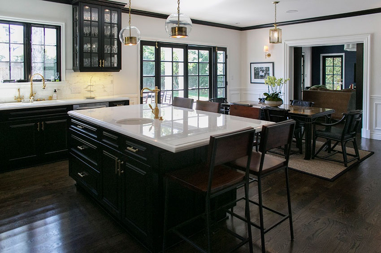 Black And White Kitchen With Black Cabinets Paired With White Marble  Countertops And White Marble Subway Tile Backsplash.