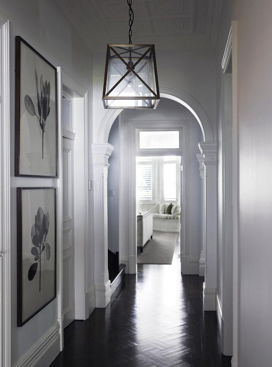 Foyer Features Hall Accented With Arched Doorways And Large Floral Prints As Well Glass Metal Pendant Over Dark Parquet Wood Floors
