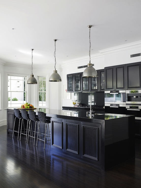 Black Kitchen Features Black Cabinets Paired With Polished Black Countertops  And Black Backsplash.