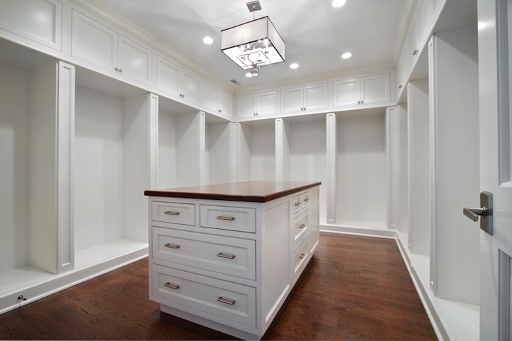 Walk-in closet features square light pendant over closet island topped with  wood top as well as floor to ceiling cabinets.