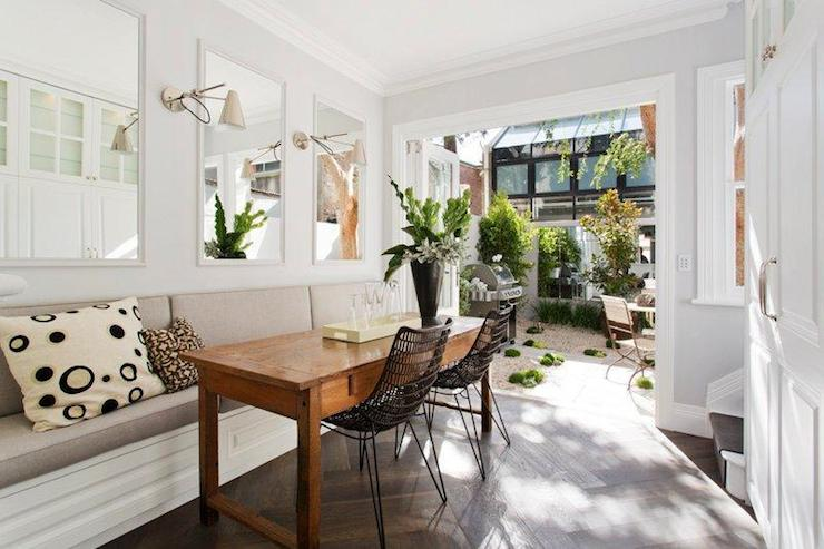 Long Dining Room Features Framed White Mirrors Over Built In Banquette Accented With Gray Cushions Paired Desk Used As Table And Metal