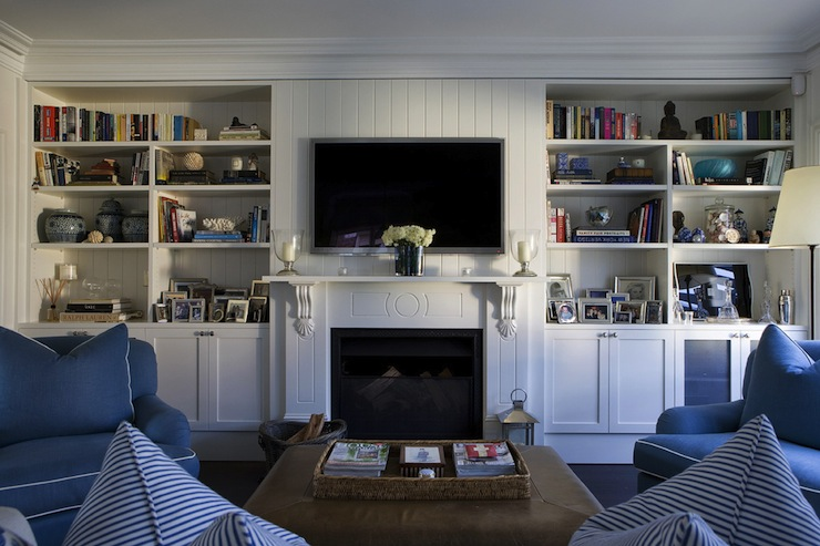 Fabulous blue and white living room with beadboard backed bookcases and fireplace topped a with flat screen tv over white corbel mantle and black fireplace screen.