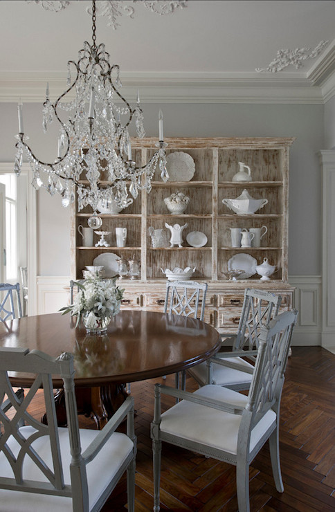 French Dining Room Features Crystal Chandelier Over Round Table Surrounded By Gray Chairs Wood Herringbone Floor