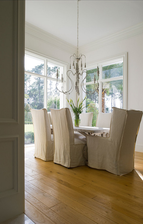 Slipcovered Dining Chairs Chic Room Features Gray Candle Chandelier Over Trestle Table Surrounded By