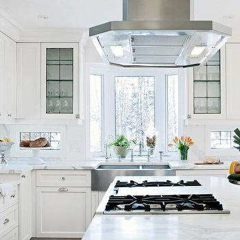 Sunny kitchen features range hood over gas cooktop on kitchen island
