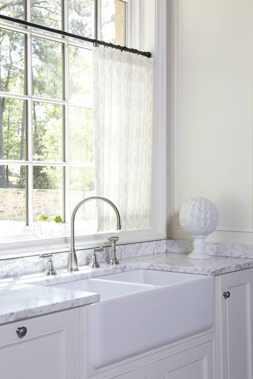 Crisp White Kitchen Cabinets Pair With Nickel Hardware Below A Carrara  Marble Counter Which Frames The Farmhouse Sink With Gooseneck Faucet.