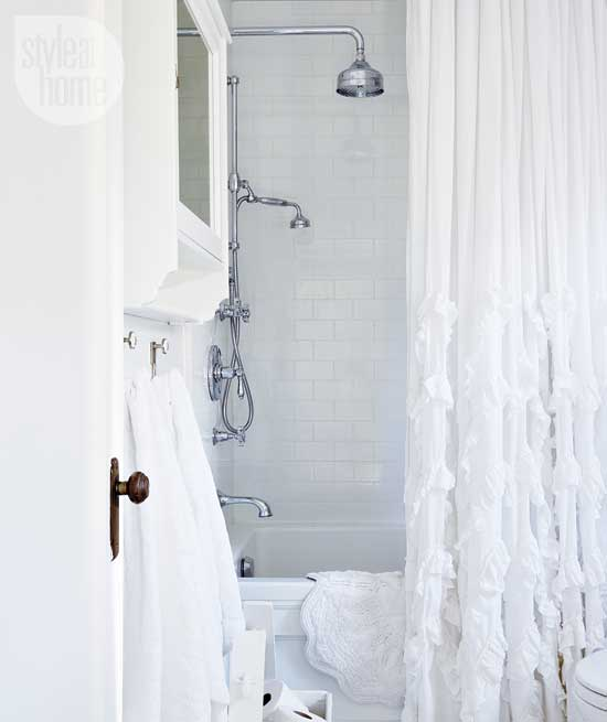 White Bathroom Features Drop In Bathtub Accented With Subway Tile Shower Surround Rain Head Exposed Plumbing And Ruffled Curtain