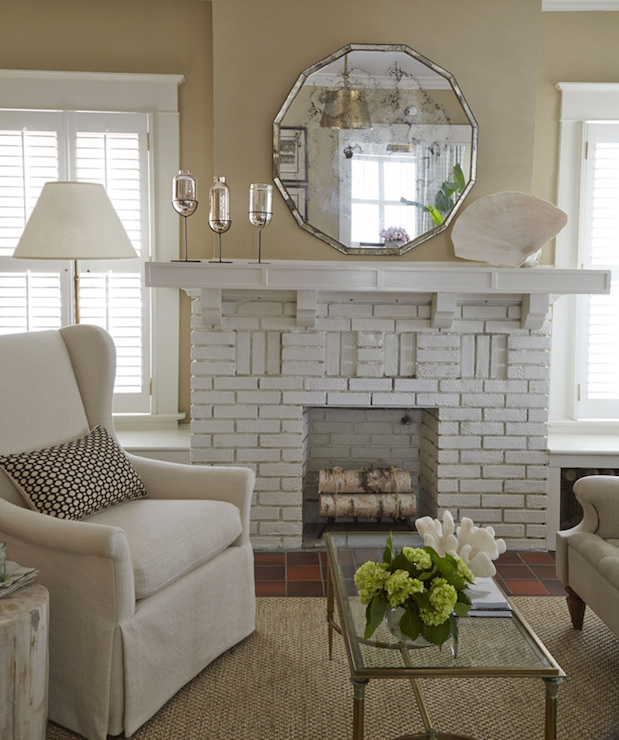 Cottage living room features antiqued mirror over white brick fireplace as well as linen slipcovered wingback chair accented with ivory and brown geometric pillow next to rustic tree stump table paired with French coffee table with glass top over jute rug.