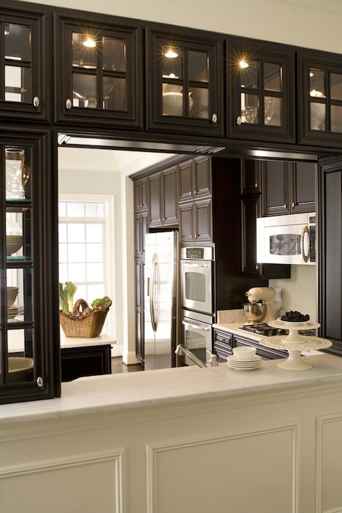 Elegant Kitchen With Espresso See Through Glass Cabinets Over White Marble Topped Pass