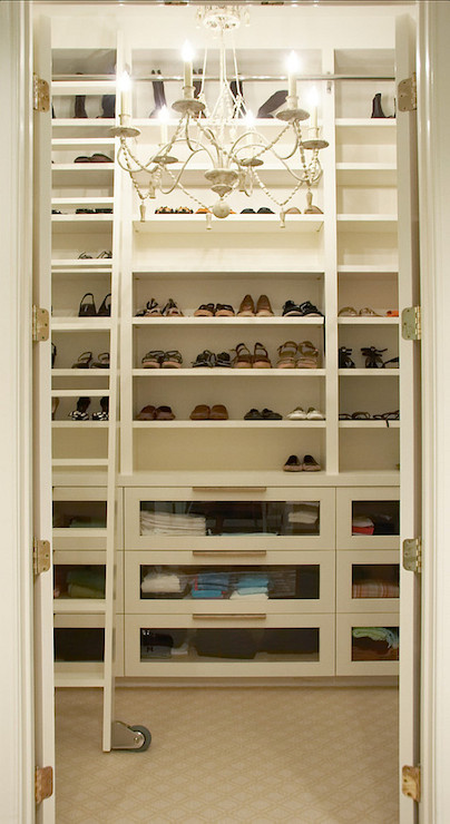 Dream Closet With Double Doors Leading To Gl Fronted Built In Dresser Drawers Below Ceiling Height Shoe Shelves Illuminated By A White Chandelier Over