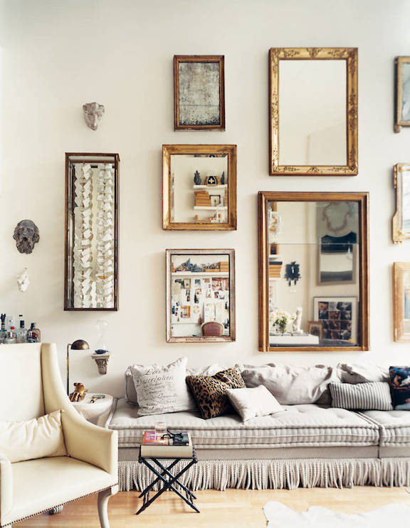 Stunning living room with collection of gold leaf mirrors over armless ...