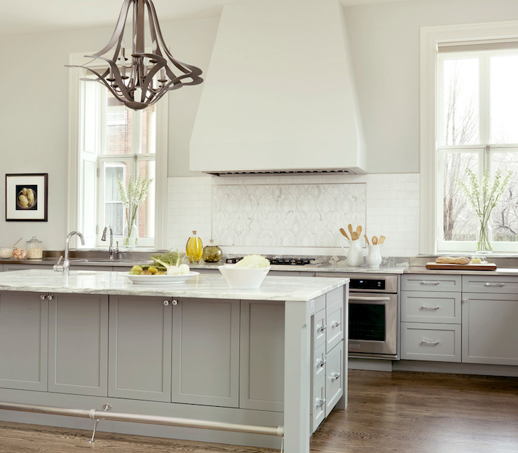 Gray kitchen features gray cabinets paired with white and gray