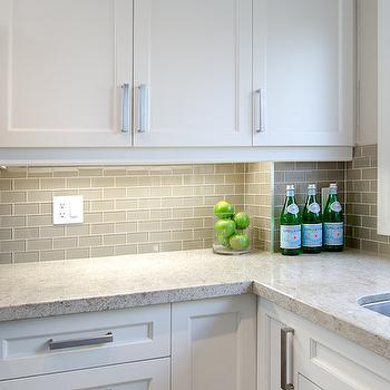 with speckled countertops and gray glass mini subway tile backsplash