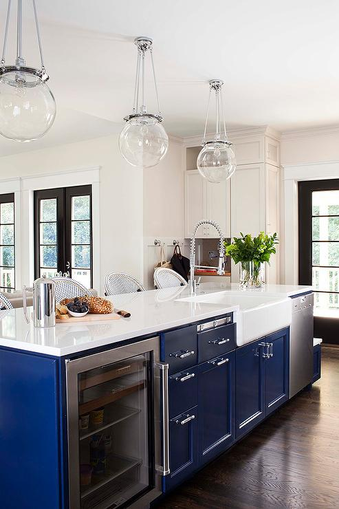kitchen features clear glass globe pendants over blue kitchen island