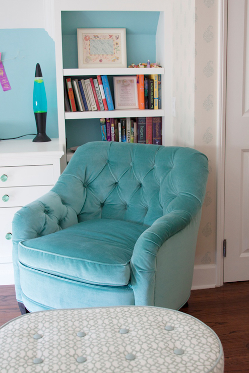 teen girls room features wall of built in bookcases with backs of bookshelves painted turquoise blue framing turquoise velvet tufted chair paired with