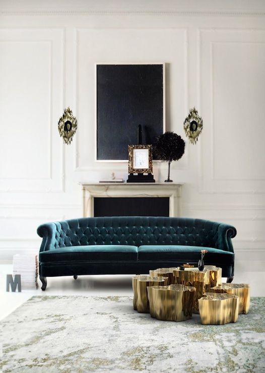 chic living room with art over marble fireplace framing peacock blue velvet tufted sofa paired with gold stump tables on overdyed rug