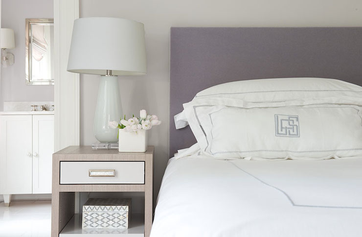 purple and gray bedroom features gray walls framing purple headboard accented with white and purple monogrammed bedding next to twotone nightstand topped