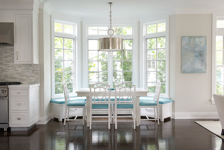 window seat accented with turquoise cushions paired with white dining