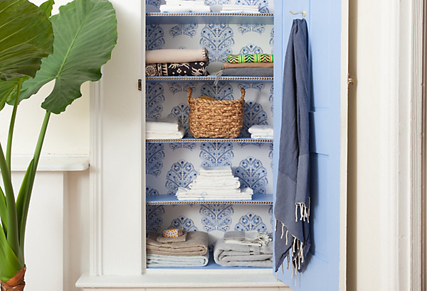 Sunny Bathroom With Potted Elephant Ear Plant Beside Linen Closet With Door  And Shelves Painted In Benjamin Moore Summer Blue.