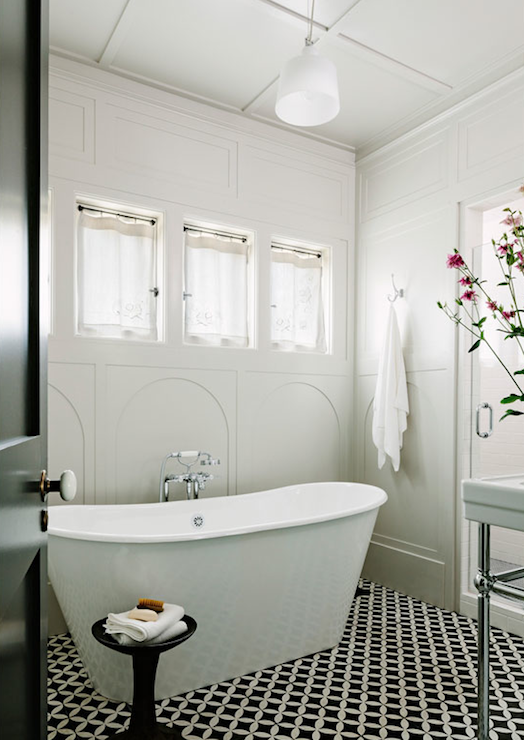 Black And White Bathroom With Decorative Paneled Wall Over Black And White  Interlocking Circle Patterned Floor Tile.