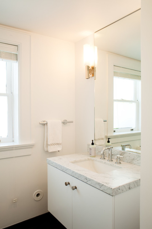 Sleek white bathroom with ceiling height frameless mirror over white  floating vanity topped with white marble countertop. Ceiling Height Bathroom Mirror Design Ideas