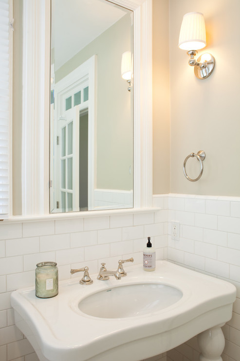 Lovely Bathroom Features Cafe Au Lait Paint On Top Half Of Walls And Subway  Tiled On Bottom Half Of Walls Framing Framed Mirror Over Parisian Pedestal  Sink.