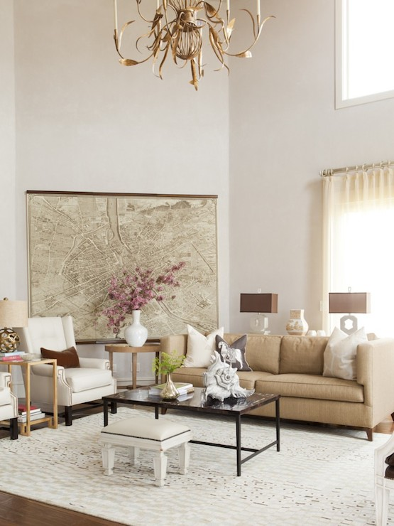 Two Story Living Room Features Vintage Map Art Framing Beige High Back Sofa Paired With White Wingback Leather Chairs Flanking Greek Key Table Topped