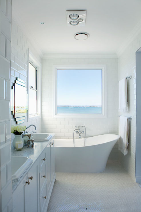 freestanding tub with faucet deck. Monochromatic beach bathroom with freestanding tub wall mounted faucet  below large picture window framed by ceiling height beveled subway tile Bathtub Under Window Transitional Cameo Homes