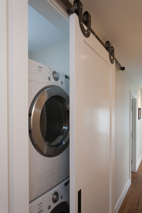 Great Hall Laundry Room Features Sliding Barn Door Concealed Stacked Washer And  Dryer.