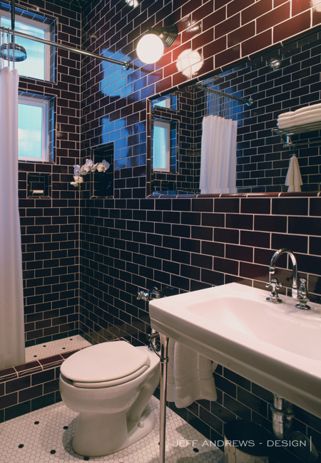 Masculine bathroom with walls tiled in dark brown subway tile highlighted by white grout over white hex tiled floors with black dot accent.
