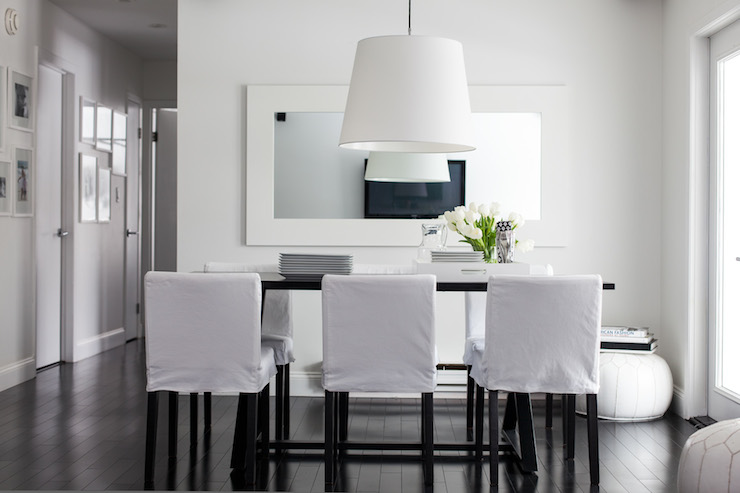 chic dining room features white pendant light over bar height dining table ikea stornas bar table lined with white slipcovered barstools ikea henriksdal