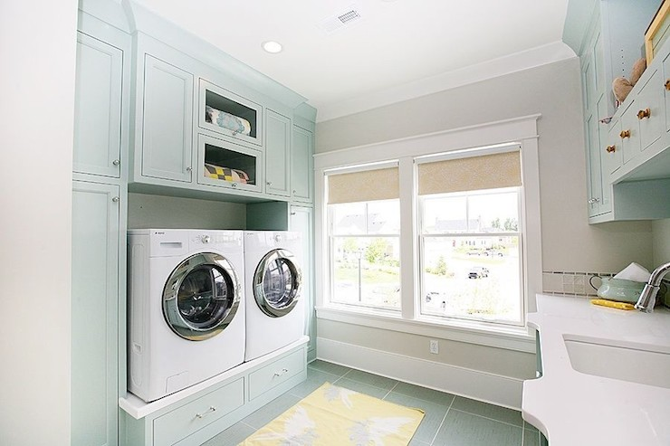 Fabulous laundry room features cabinets painted blue  Benjamin Moore  Palladian Blue  surrounding front load washer and dryer on built in risers  across from. Palladian Blue Design Ideas