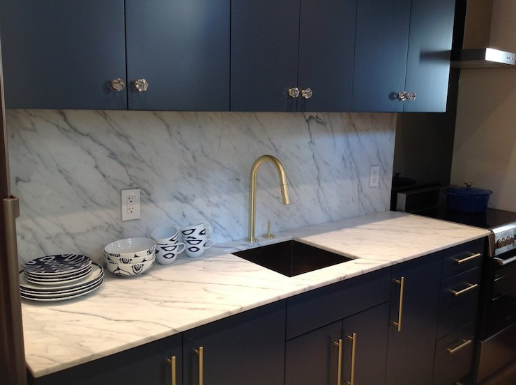 Contemporary Kitchen Features Navy Blue Cabinets Paired With Statuarietto Vintage Marble Countertops And Backsplash