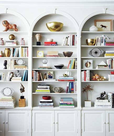 Living Room With Arched Bookcases Filled Tchotchkes Situated Above Built In Cabinets