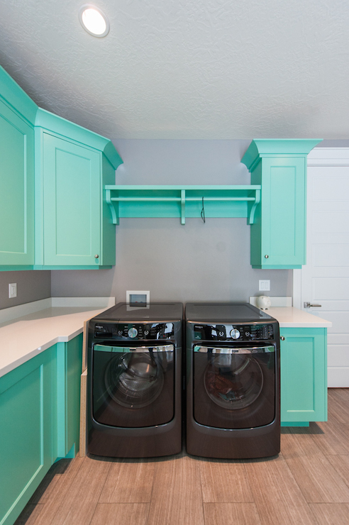 Fun Laundry Room Features Teal Cabinets Paired With White Countertops And Gray Paint As Backsplash