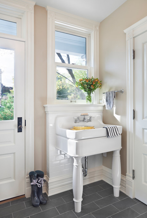 Cottage Laundry Room Features Beige Walls Framing 2 Leg Utility Sink Paired  With Vintage Style Faucet Leaning Against Subway Tiled Half Wall Backsplash  Over ...