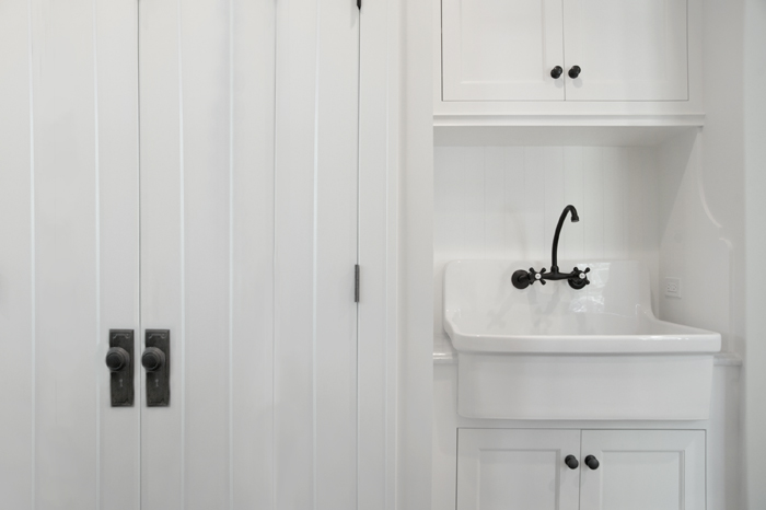 monochromatic laundry room with white wood paneled closetdoors alongside a white vanity with wall mounted utility sink paired with an oil rubbed bronze