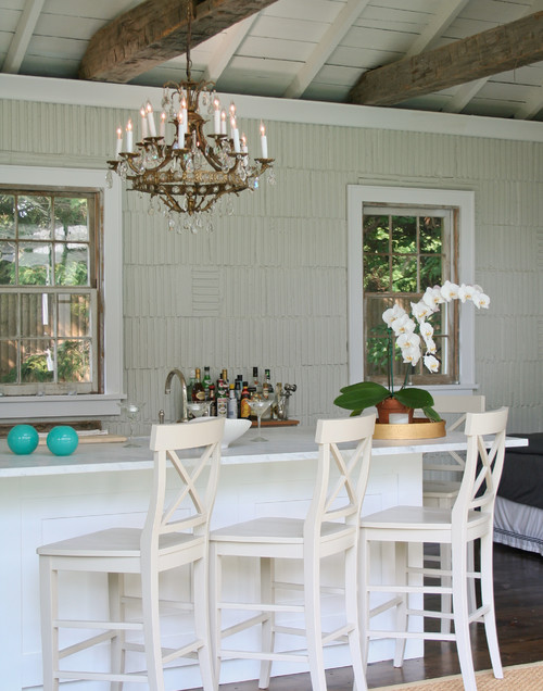 Gorgeous kitchen with gilt candelabra style chandelier hung from rustic  wood beamed vaulted ceilings over a long white kitchen island with white  counter ...